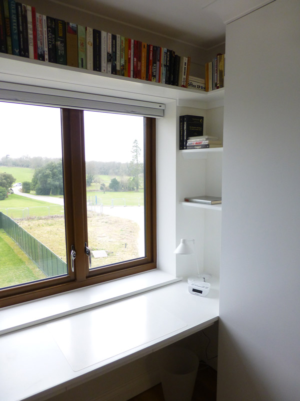 The work area includes bespoke filing drawers and low profile pencil