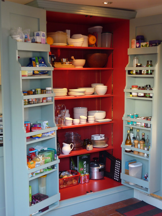 interior of handmade kitchen larder cupboard showing door racks